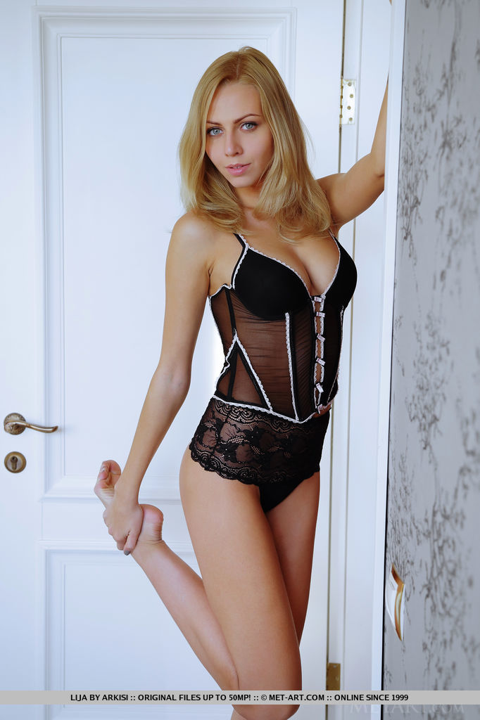 blond girl with big breasts which have black body lingerie with white accents for hot night in the bedroom