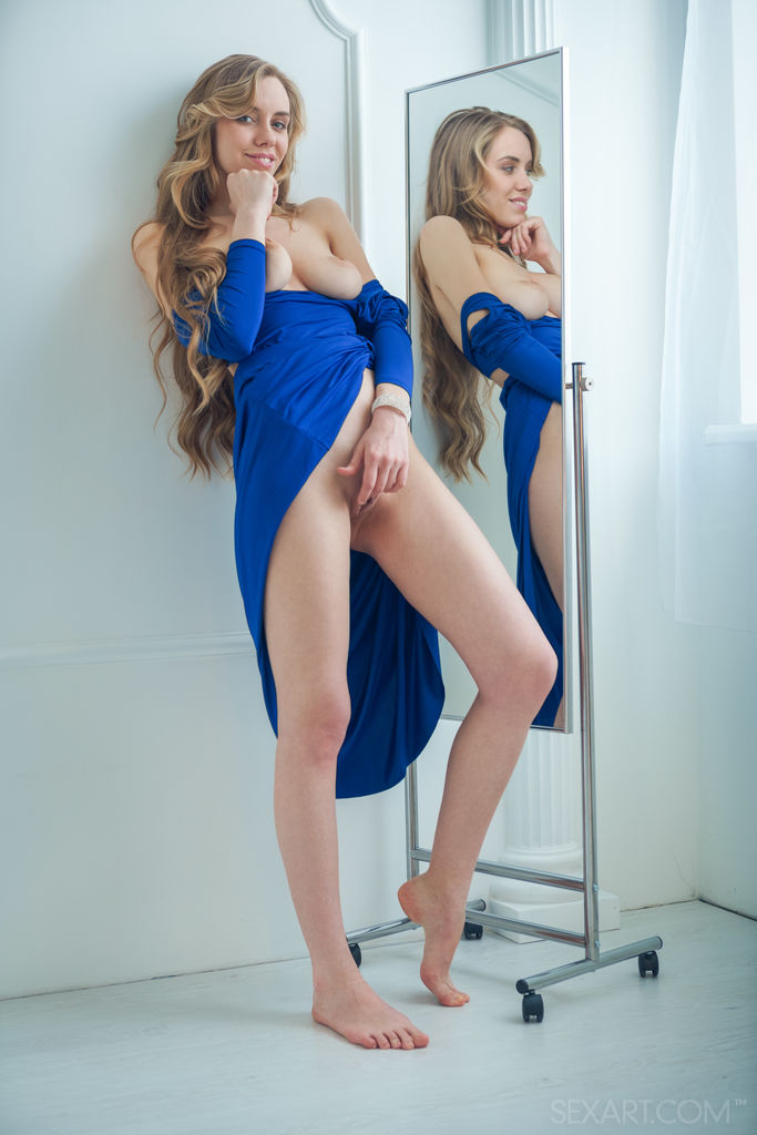 Ryana the girl is wearing a blue dress and has big boobs exposed and is holding her pussy with her hand