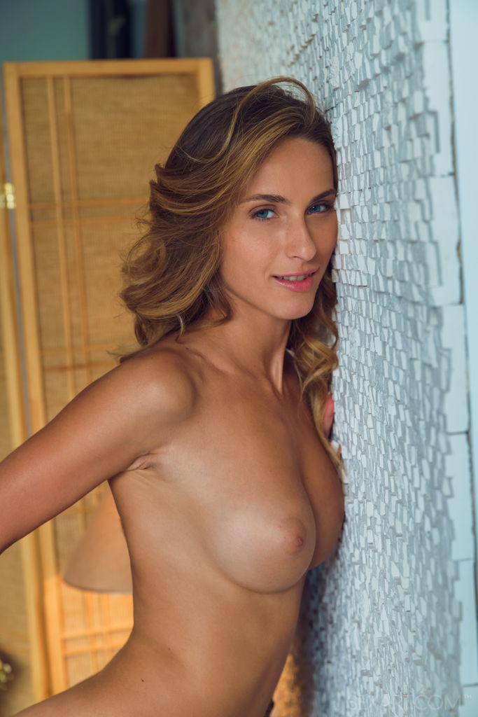 Cara Mell tanned woman leans against the wall so that her breasts are pressed against the wall perfect position from behind for having sex