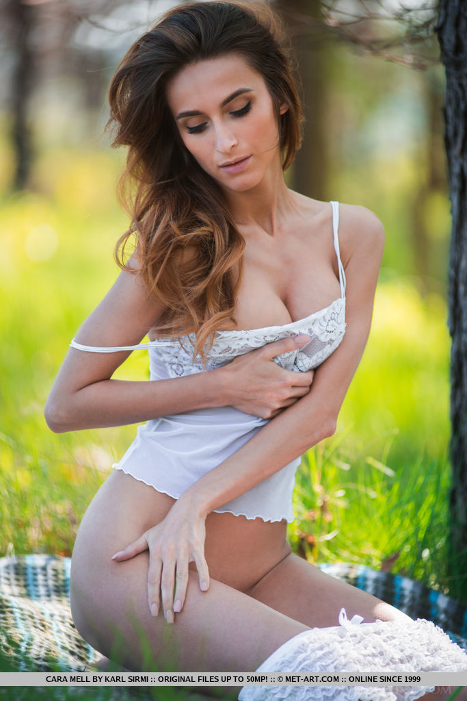 Cara Mell the woman sits in a meadow in a white sexy T shirt so that she squeezes her breasts that they look better