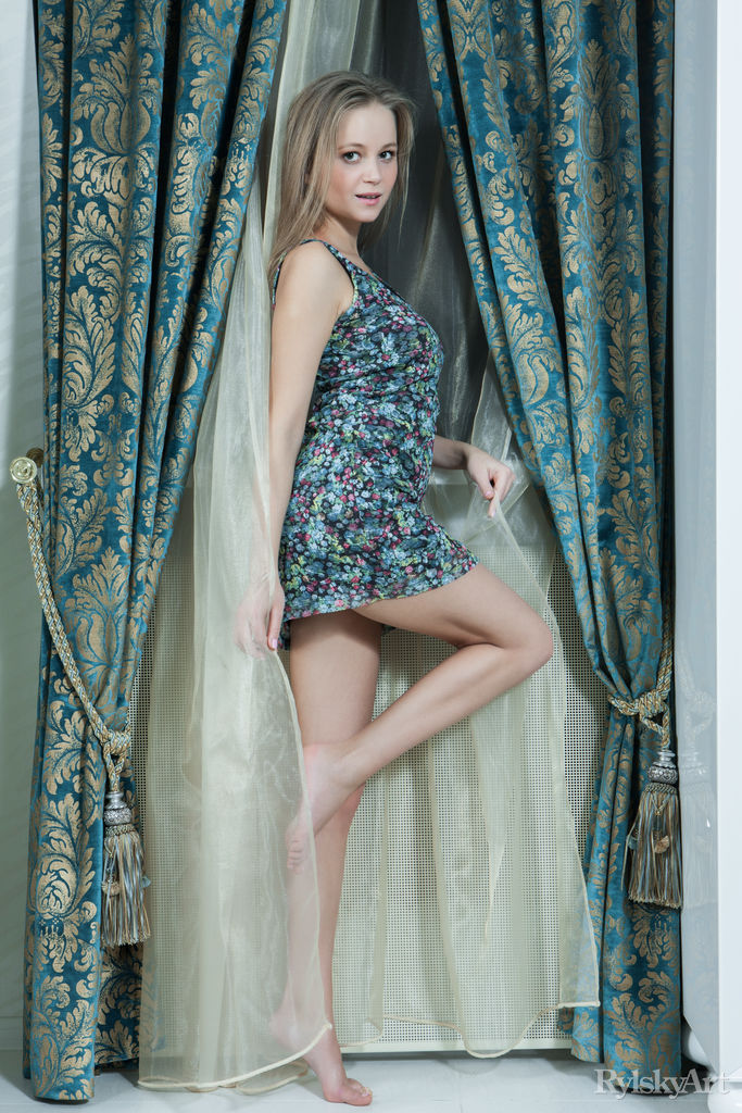 blonde in a dress on a background of curtains