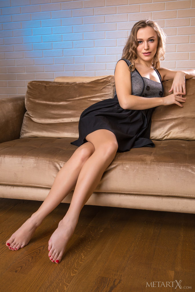Hot Aislin is sitting on the couch wearing a dress and showing off her bare legs