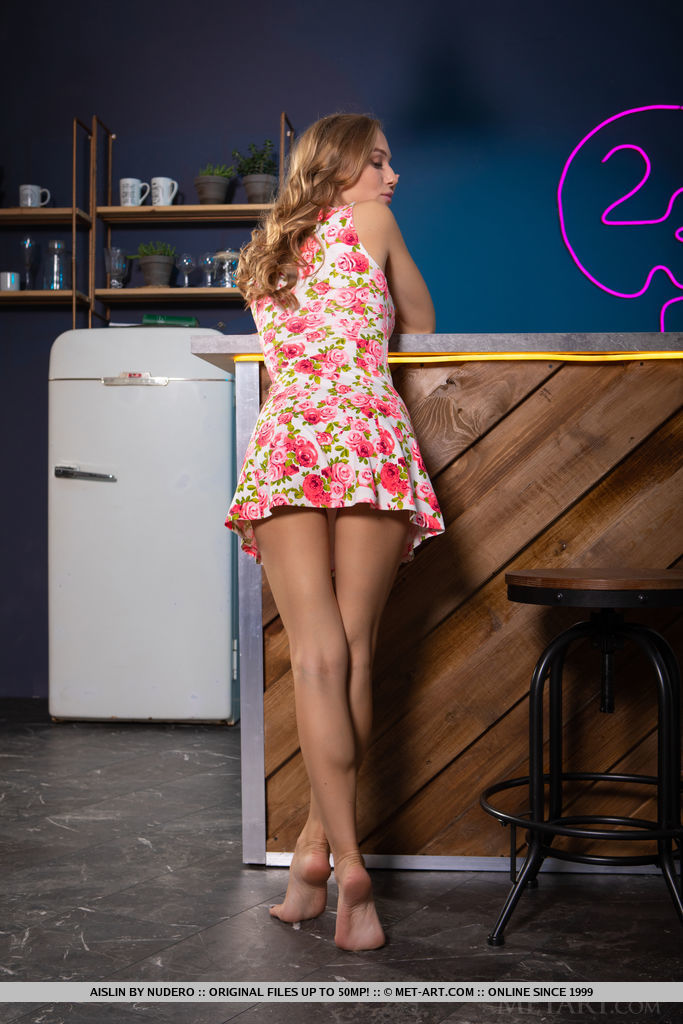 Aislin in a flower dress is leaning against the bar so that her legs and ass are tempting