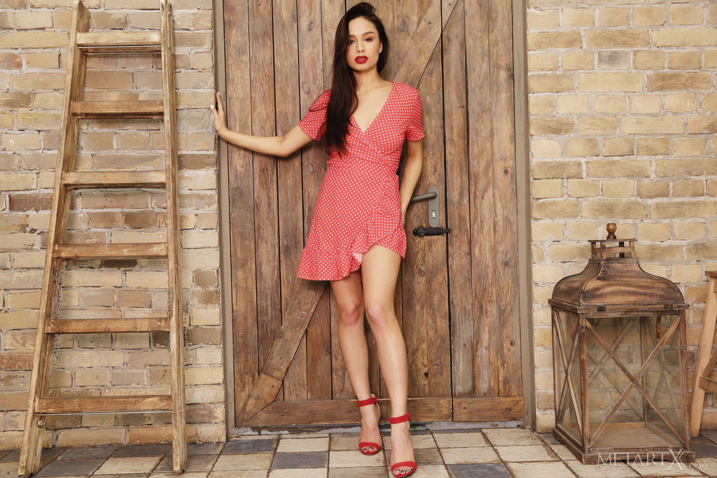 A black haired girl in a red dress with white polka dots leans against a rustic door