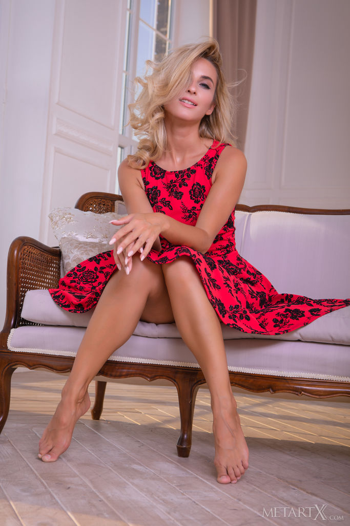 Cara Mell is sitting on the couch and she is wearing a red dress with black patterns and her bare legs are divine