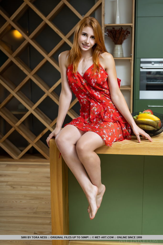 The divine red girl in a red dress sits on the kitchen counter