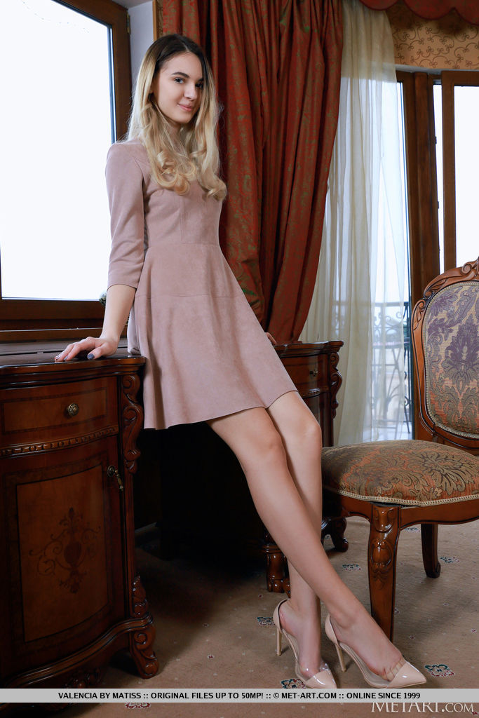 Valencia in a beige dress shows off her long legs
