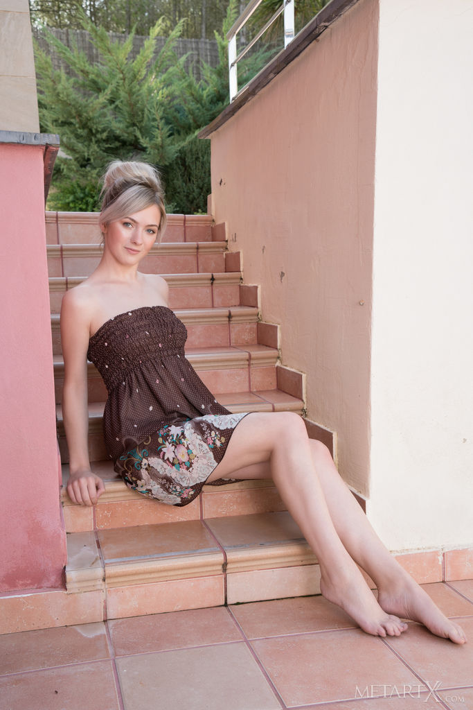 a beautiful blonde in a dark dress sits on the stairs and shows off her pretty legs