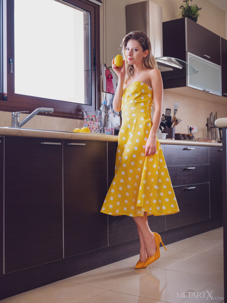 Beautiful woman wearing a yellow dress with white polka dots