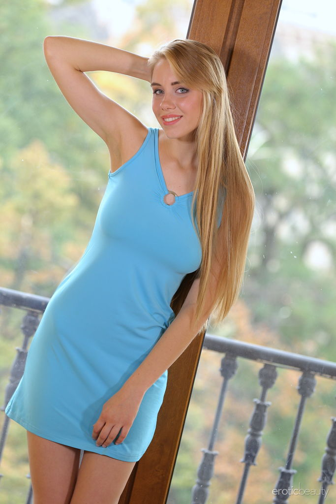 Hot blonde with long hair wearing a blue dress