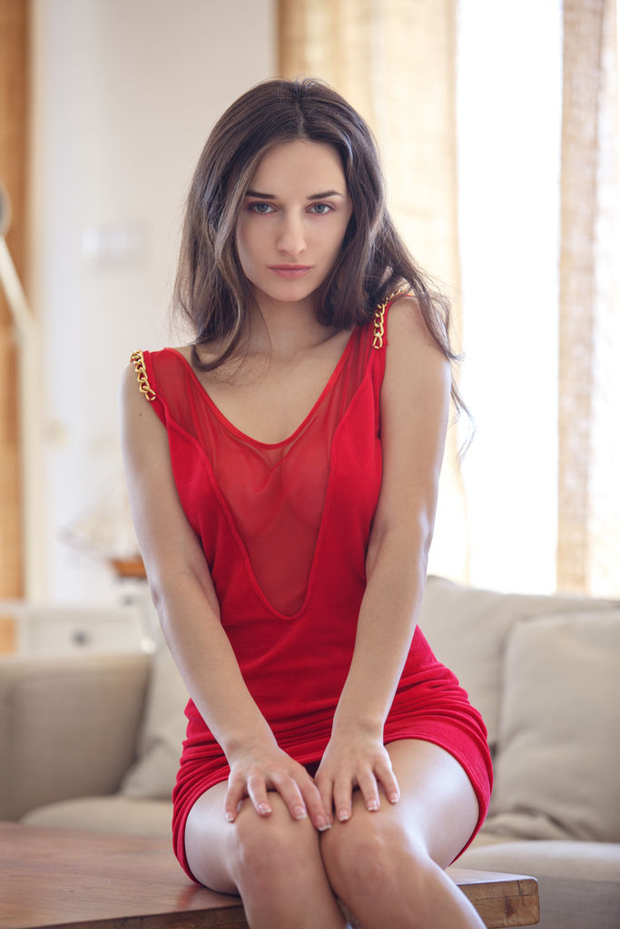 Gloria Sol wearing a red dress with a see through neckline sits so sexy that it gets hot at the sight of her