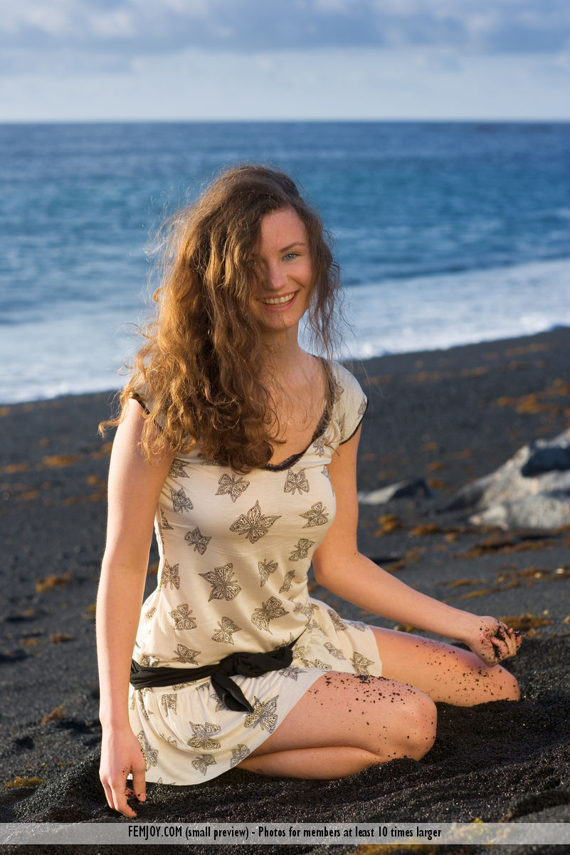 smiling girl sitting on the beach wearing a dress with black butterflies