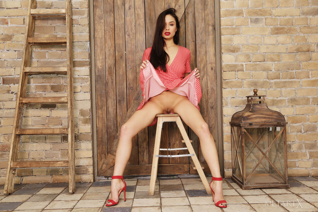 Astrid Herrara is sitting on a stool in a red dress showing what s under her skirt