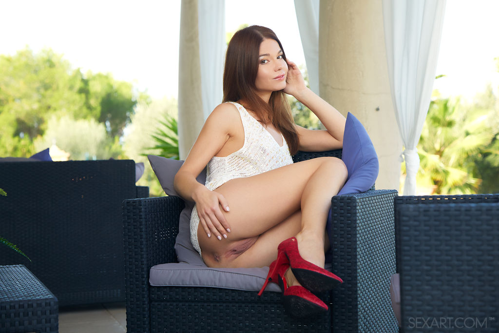 Nedda A sits on an armchair in burgundy high heels so that her pussy can be dyed with your hand