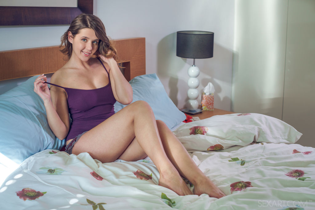 Sybil A is sitting on the sleeper bed pulling off her purple blouse to show her breasts