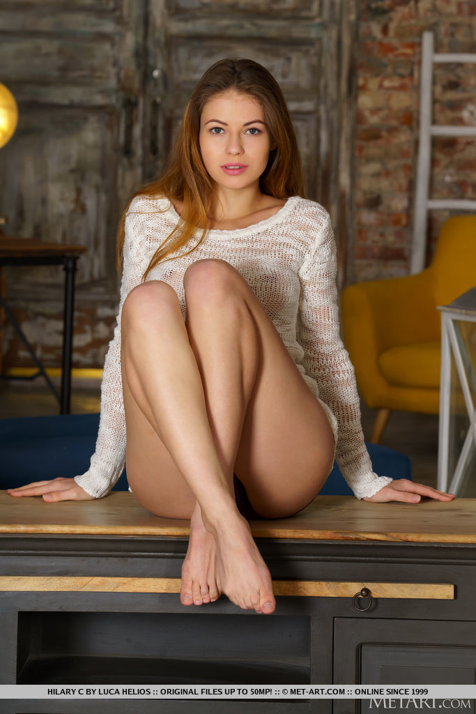 Hilary C in a white sweater covers her pussy with her legs